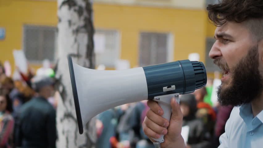 A desperate man goes and demands a megaphone on strike. European guy with a beard is yelling into the loudspeaker at a rally. People are unhappy with the government. Revolution on the street in city.