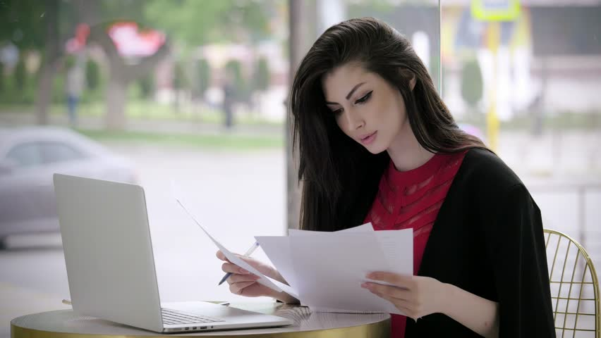 beautiful young girl in a business suit looking for a job fill out a form or resume looking at the laptop sit in a cafe. concept employment and crisis. Royalty-Free Stock Footage #1017538312
