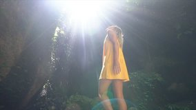 Young woman standing on rock contemplating tropical rainforest, beautiful light coming from above making sunbeams- Slow motion video- people travel nature beauty concept