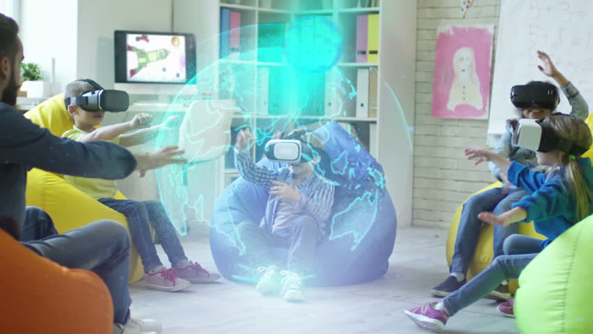 Playful little boys and girls sitting on colorful bean bag chairs, watching educational video in VR glasses and trying to touch holographic projection of Earth planet rotating in center of classroom