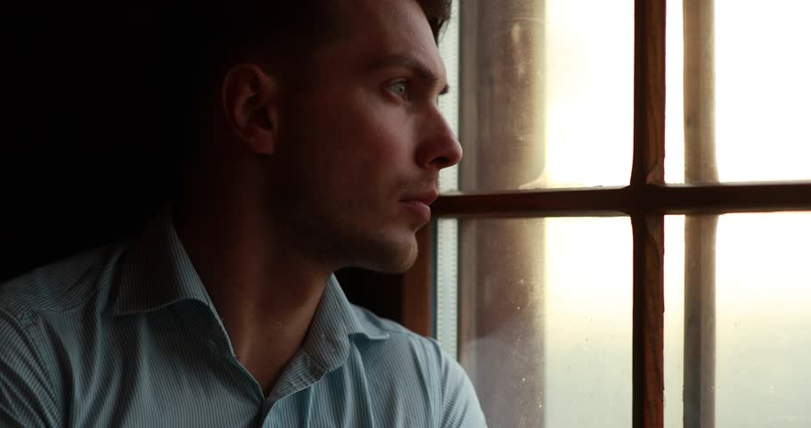 Loneliness in the mountains. Handsome young man leans to the window and closes his eyes looking at the evening mountain landscape outside