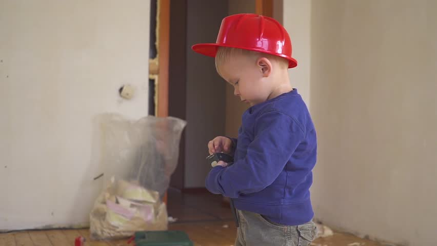 Little builder in red helmet with yellow ruler tape in hands in the apartment under repair. Construction concept. | Shutterstock HD Video #1017547273