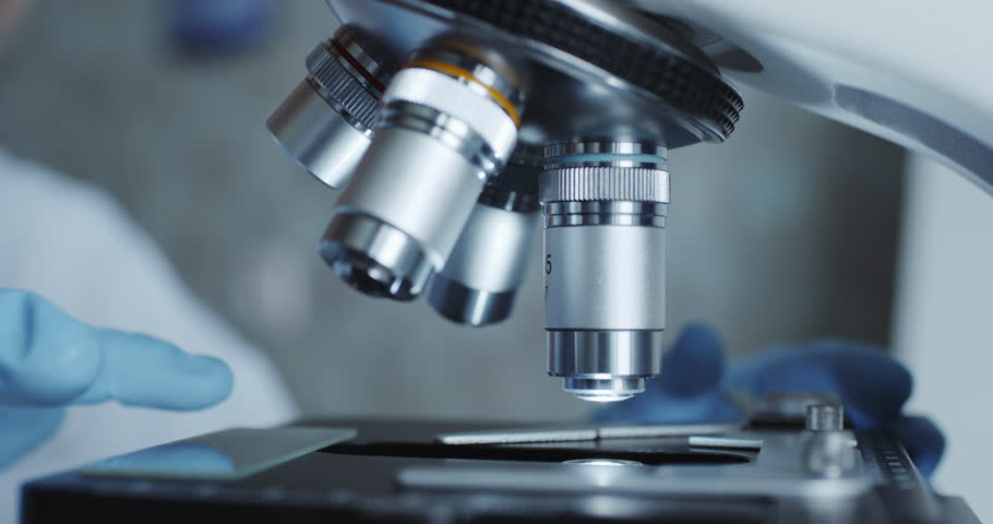 Close-up shot of sample slide and microscope with metal lens at laboratory. | Shutterstock HD Video #1017548551