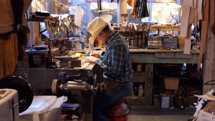 FORT WORTH, TEXAS / USA - JULY 2018: Man working as artisan in souvenir shop and painting leather belt. American cowboy at work in traditional Western store in Fort Worth, Texas, United States