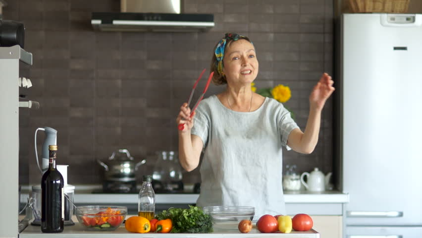 Well-groomed, beautiful middle-aged woman pensioner dancing in the kitchen with a red spatula for frying. Bright kitchen interior, on the table are vegetables. Happy secured pension | Shutterstock HD Video #1017596674