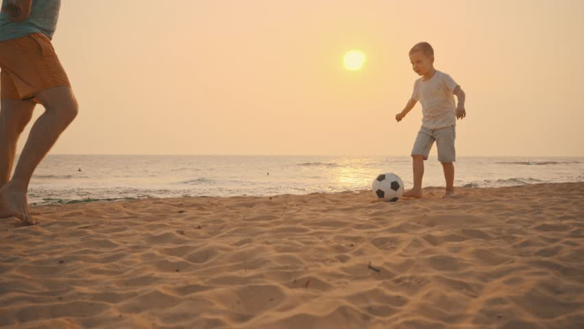 Father and son Soccer players in dynamic action funny play on the sand in beach football in summer sunny day under sunlight. #1017597697