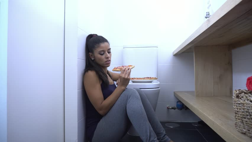 Attractive young and sad bulimic young woman feeling guilty and sick eating while sitting on the floor next to the toilet in eating disorders anorexia and bulimia concept.