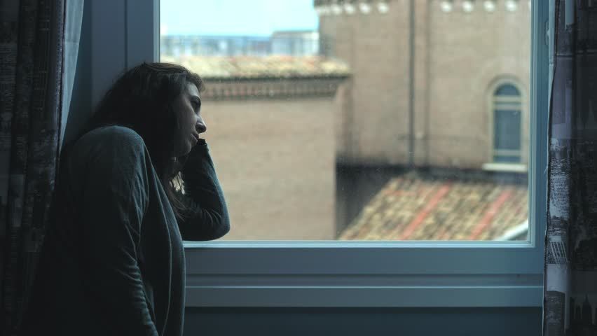 Depressed lonely young woman thinking at window. Divorce,hussband   Shutterstock HD Video #1017602401