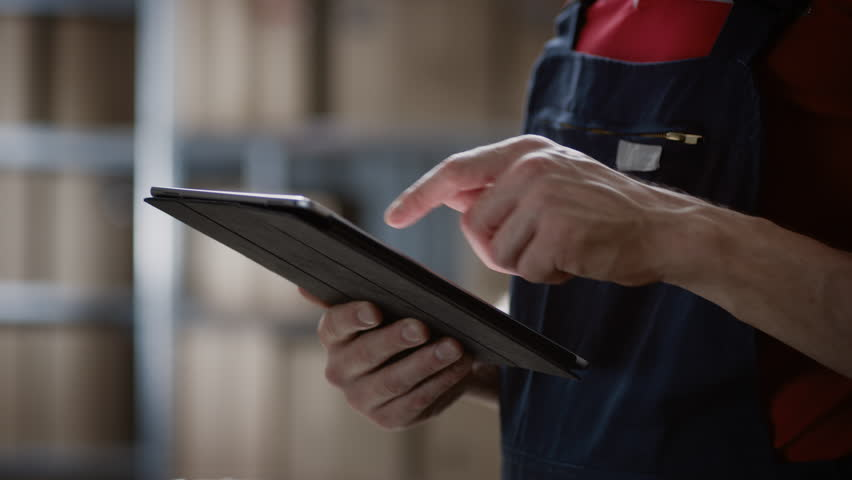 Close-up on a Man's Hands Using Digital Tablet Computer while Standing in the Warehouse.