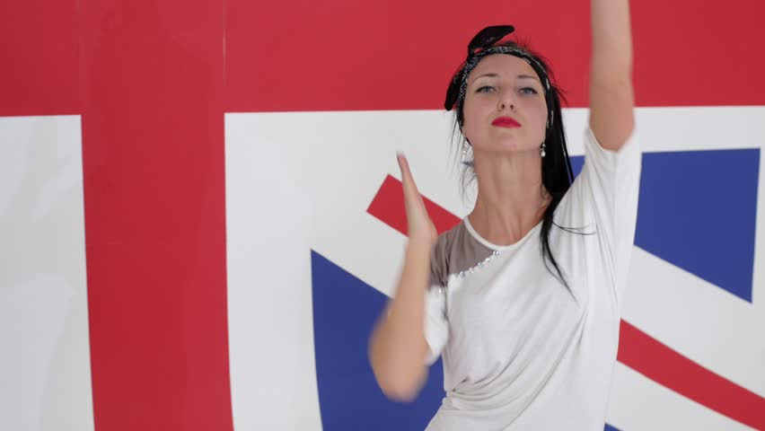 Young pretty caucasian smiling woman with long black hair , dressed in white t-shirt is looking at camera and energetically dancing on camera on background of british flag.   Shutterstock HD Video #1017612805