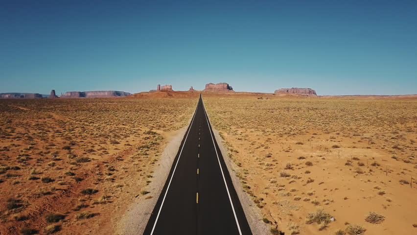 Drone flying backwards over iconic empty sandstone desert road in Monuments Valley, Arizona with big cliff mountains.