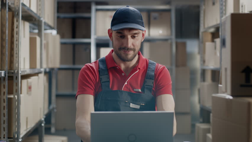 Worker Uses Laptop while Sitting at His Desk in the Warehouse.