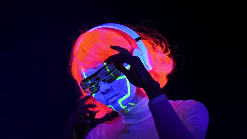 Slow motin of beautiful sexy woman with UV cyborg face paint, wig, glowing glasses, clothing dancing and listening to music with headphones. Asian woman. Party concept. | Shutterstock HD Video #1017658852