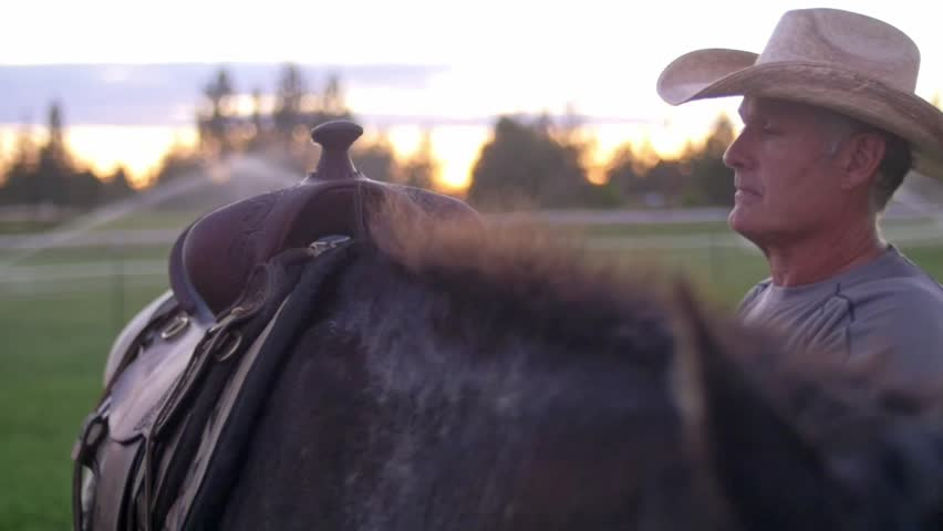 An older cowboy takes his hat off, wipes the sweat from his forehead, and places his hat back on while standing with a saddled horse | Shutterstock HD Video #1017676024