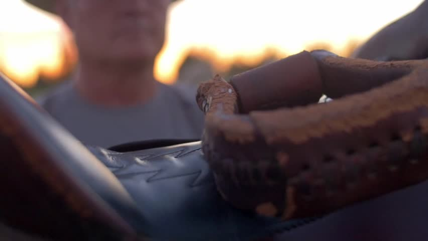Close-up shot of an older man unstrapping the leather saddle on a horse during sunset | Shutterstock HD Video #1017676039