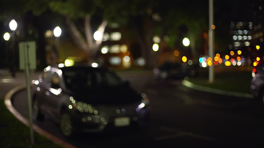 Bokeh shot of cars parked on a quiet street in California city. Out of focus video backdrop of parked cars downtown at night for compositing. 4k