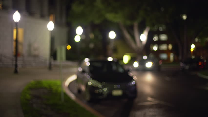 Out of focus video background plate of parked cars on quiet street at night. Car driving through State Capitol grounds. 4k