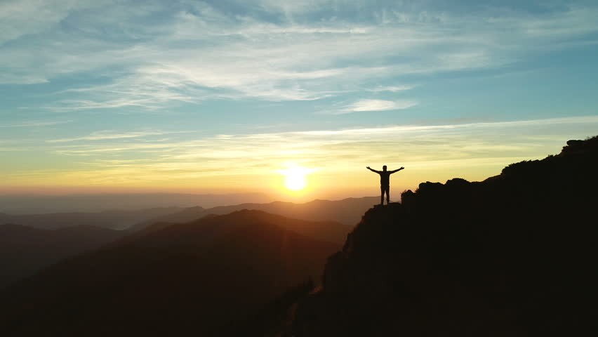 The man standing on the cliff on the sunset background   Shutterstock HD Video #1017696373