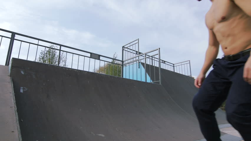 Skater make trick rock n roll on the edge of quarter pipe in wooden skatepark