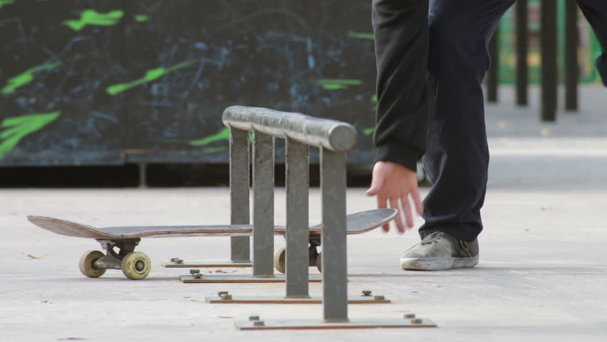 Skater fails the trick on rail, bring up skateboard and going try again, slowmo