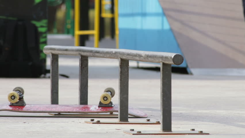 Skater takes a skateboard and tries the trick on the rail in skatepark, slowmo