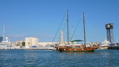 BARCELONA, SPAIN - AUGUST 14, 2018: Wooden touristic boat sail at Barcelona Harbour, Clock tower and piers on background. Popular tourist attraction, regular shot trip around city port