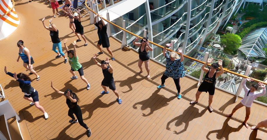 """FORT LAUDERDALE, FLORIDA, USA - SEPTEMBER 23, 2018: Tourists and crew members of the """"Harmony Of The Seas"""" Royal Caribbean cruise ship dancing on the top deck in Fort Lauderdale, Florida, 4K"""