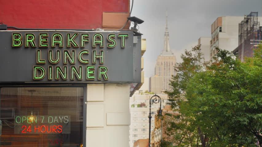 A daytime exterior establishing shot of a city corner diner's neon sign in midtown Manhattan.  | Shutterstock HD Video #1017741742