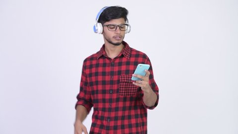 Young happy bearded Indian hipster man listening to music while using phone