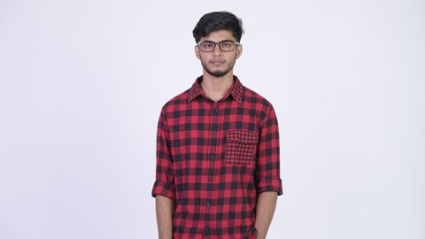 Young happy bearded Indian hipster man pointing up