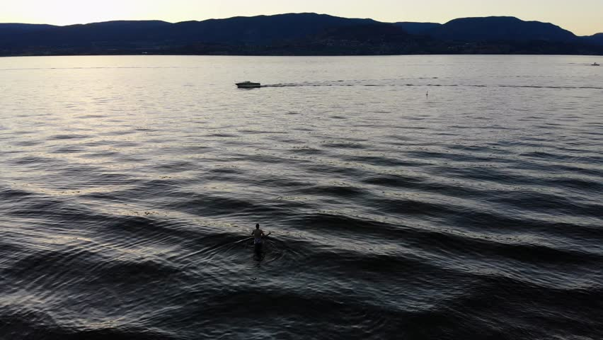 Aerial Drone View Of Man Walking In Lake At Sunset By Motor Boat