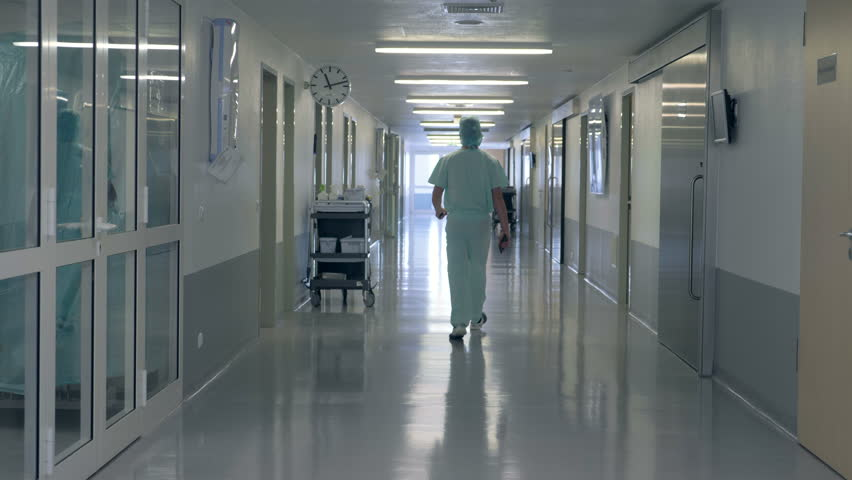 A man walking in a clinic hall. Person in doctor uniform walks in a hospital building. | Shutterstock HD Video #1017757159