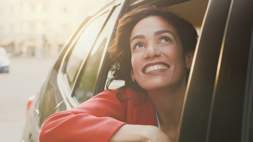 Happy Beautiful Woman Riding on a Back Seat of a Car, Looks out of the Open Window in Wonder of the Big City. Traveling Girl Experience Magic of the World. Camera Shot Made from Outside the Vehicle.