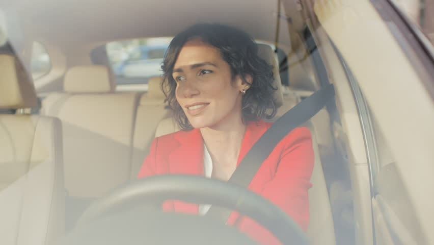Portrait of beautiful Young Woman Driving Car through big Sunny City. Camera Shot Made From the Front Windshield. Royalty-Free Stock Footage #1017759634