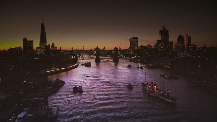 Dramatic aerial view of River Thames & Tower Bridge, steamboat on clear night full of sparkle stars.