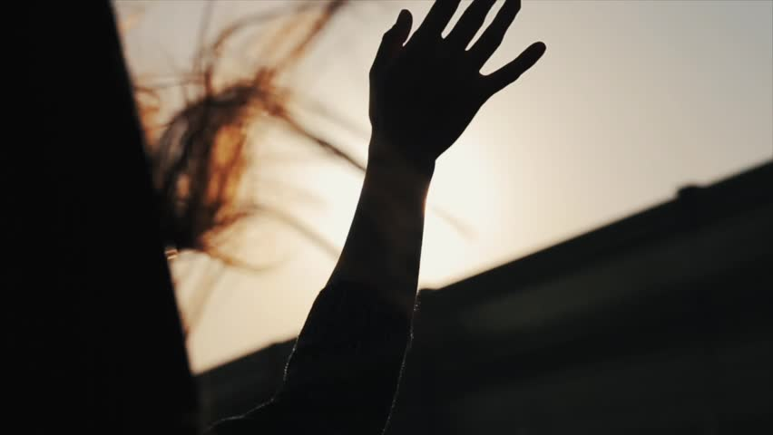 A female riding a car and holding her hand out of the window. Her hair is flying in the wing. Close view. Back view