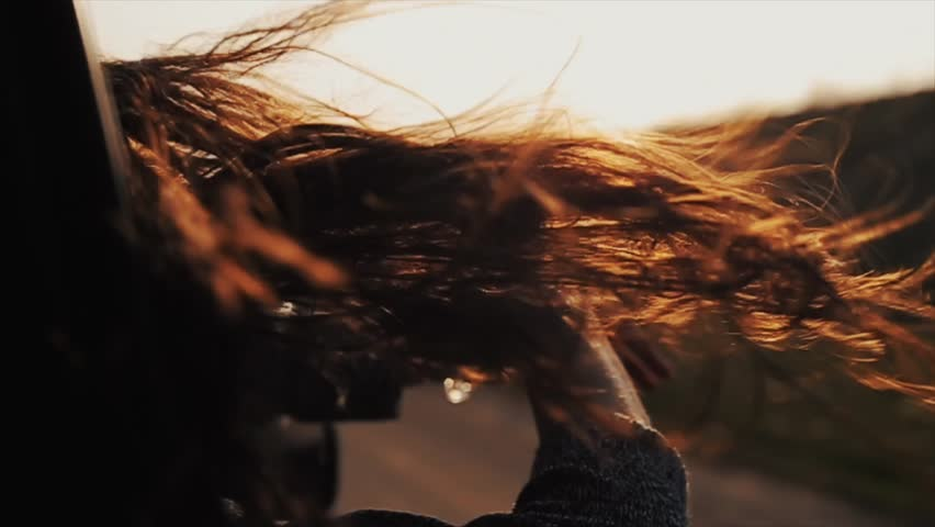 Close view of girl s long hair waving by wind and her hands playing with them while she is riding a car and looking out of the window. Rear view