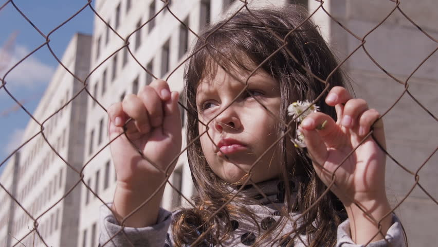 Homeless child. Portrait of a homeless child. Refugee camp. Sad little girl behind the fence.  Child abuse. | Shutterstock HD Video #1017787315
