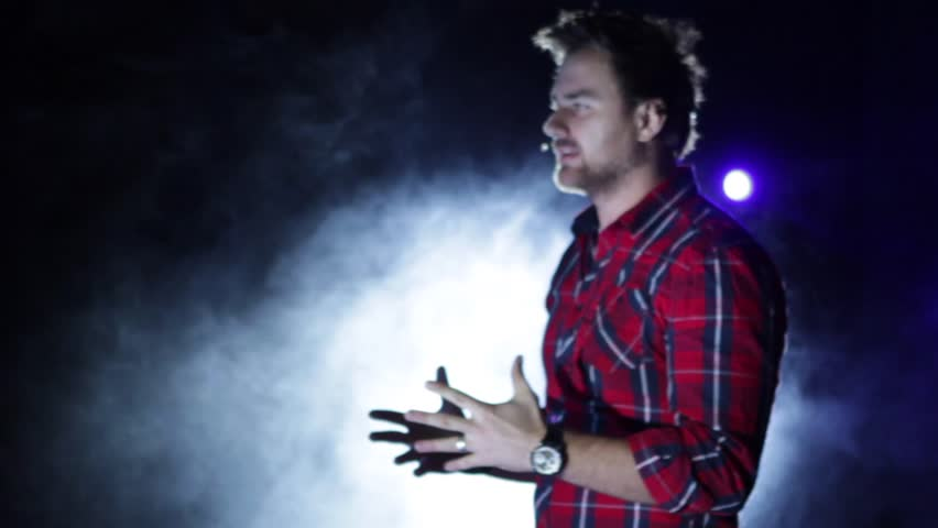 A young man talking to a crowd on a concert. Lighting. A young caucasian man talking to a crowd on a concert.