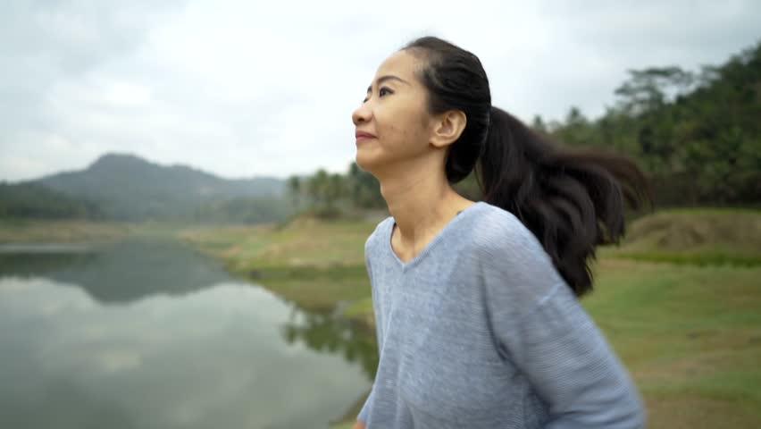 Portrait woman enjoy jogging on side the river   Shutterstock HD Video #1017790210