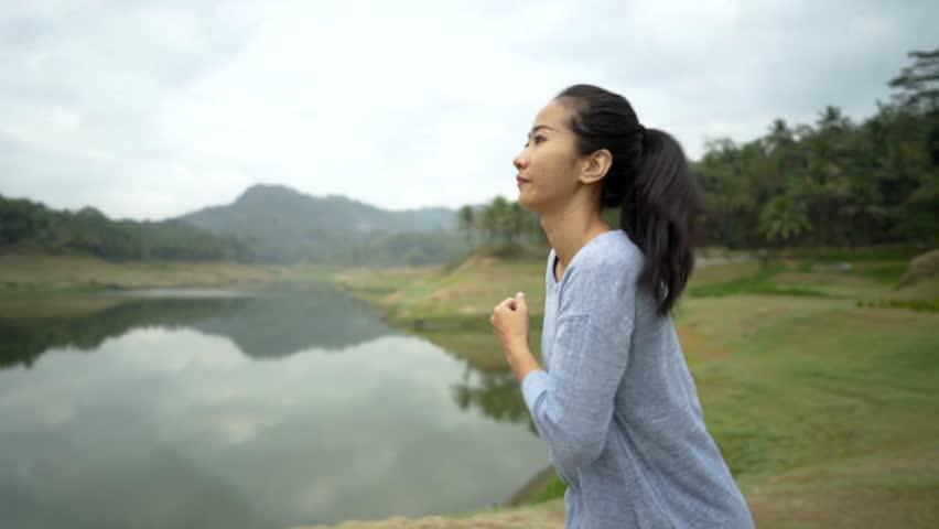 Asian woman enjoy jogging on side the river, lake background   Shutterstock HD Video #1017790219