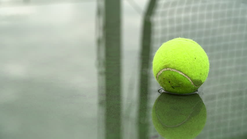 Close up of a somewhat ragged tennis ball in a puddle.  Green surface court.  Net reflected in the water.  Left to right pan.  No people.  Cloudy day. #1017790432