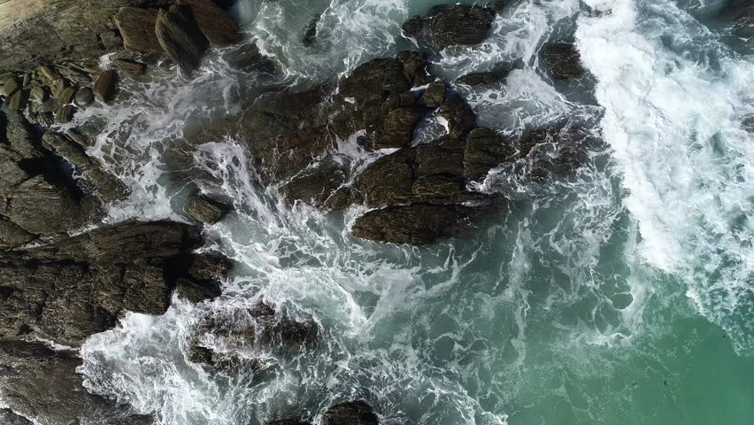 Aerial view of ocean waves and fantastic Rocky coast at New Zealand. Danger sea wave crashing on rock coast with spray and foam before storm in Brighton Beach, New Zealand.