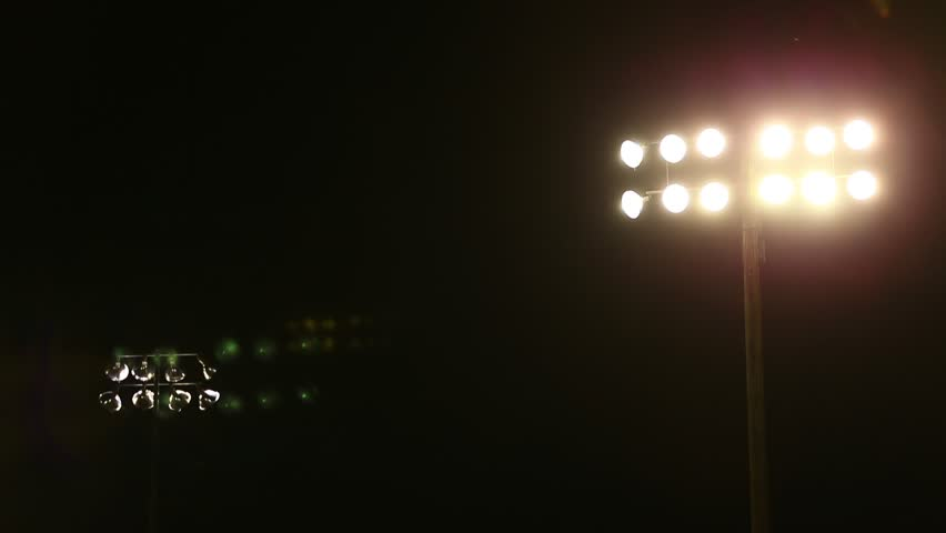 Stadium Lights at High School Football game on Friday Night.  Night Scene, dark with lights and lens flares from lights.