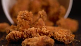 Tub of chicken wings tilting and falling spilling the crispy crumbed meat onto the table in a close up view