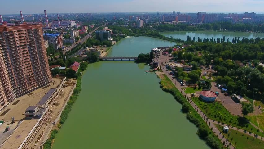 Descend green park and birds flying away. Aerial footage over city Krasnodar River Kuban and Central Park view from top. Krasnodar summer green trees bridge, multi houses skyline visible in distance. | Shutterstock HD Video #1017803446