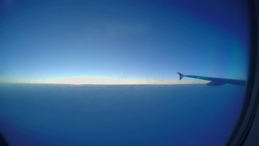 Passenger airliner flying at thousands feet height. Sun rising through clouds #1017805402