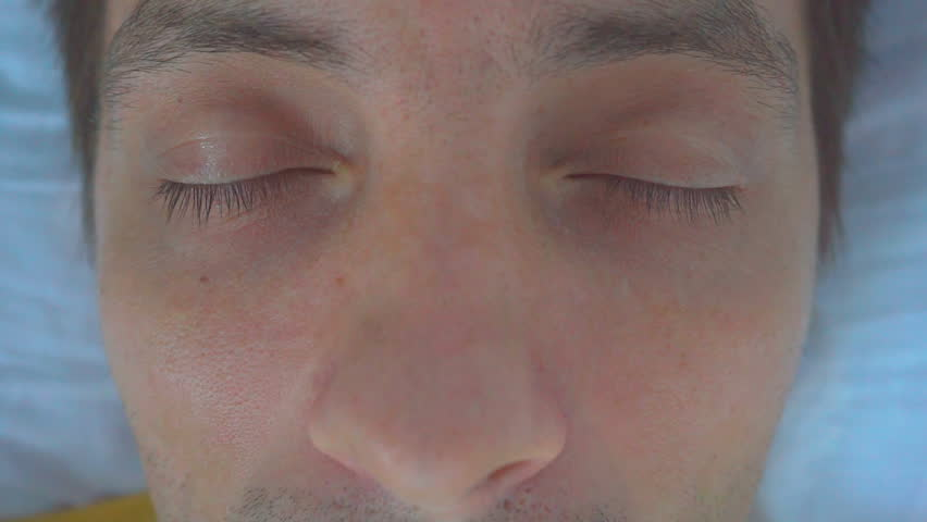 Man abruptly opens his eyes in a hospital bed. | Shutterstock HD Video #1017816730