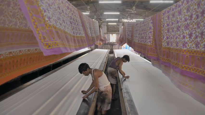 A moving shot of a daily wage workers or laborers working in textile printing interior factory setup while colorful printed cotton sheets hanged on the top to let them dry