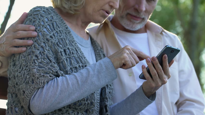 Mature couple easily coping with modern smartphone, easy to use applications